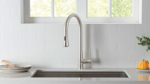 white back splash with stainless steel kitchen faucet