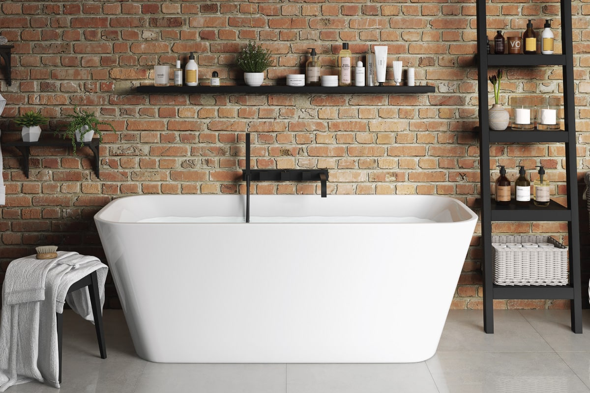 Rustic farmhouse bathroom with tub and brick wall